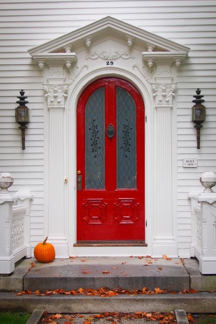 wallpaper portable pour halloween avec photo de maison à façade blanche et porte rouge à décoration citrouille