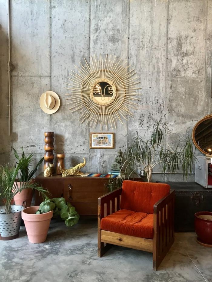 salon aux murs béton aménagé avec meubles en bois marron foncé et plantes d'intérieur, diy miroir osier ovale