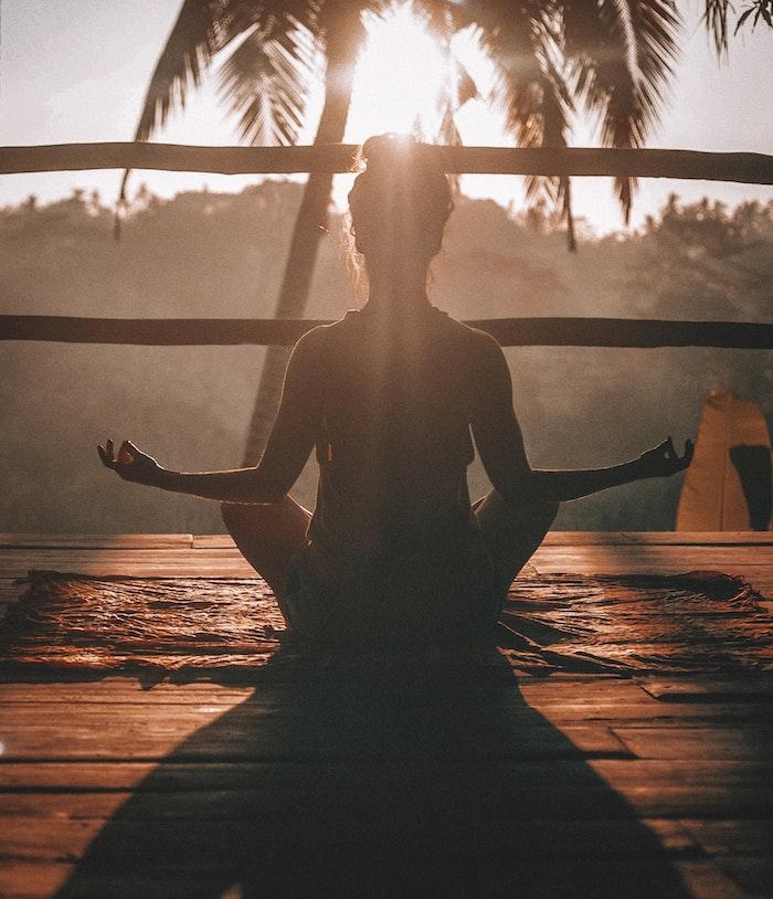 Sport pour 7 minutes par jour, idée comment se sentir bien, femme qui fait de yoga dans sa terrasse avec vue de la mer et palmiers