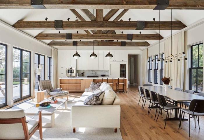 exemple de grange rénovée de style moderne, idée aménagement cuisine ouverte, décoration salle à manger table blanc et chaises grises