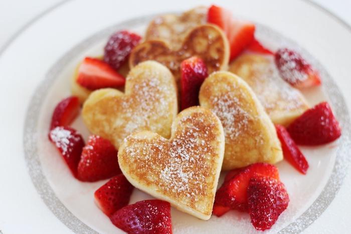 idee de repas petit dejeuner saint valentin, crepes en forme de coeur originale garnies de sucre glace et fraises