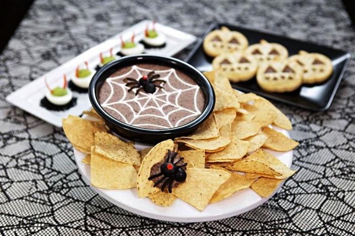 recette d'halloween facile pour préparer du houmous aux haricots noirs, houmous toile d'araignée servi avec chips tortillas