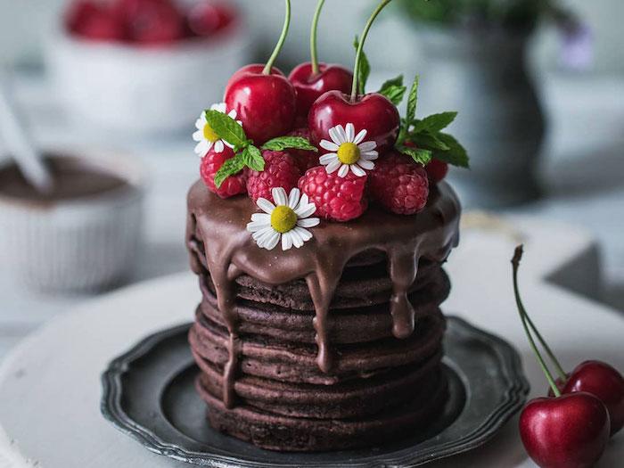 idee de crepes double chocolat avec glacage chocolat et topping de framboises et cerises fraiches, deco de fleurs, photographie culinaire