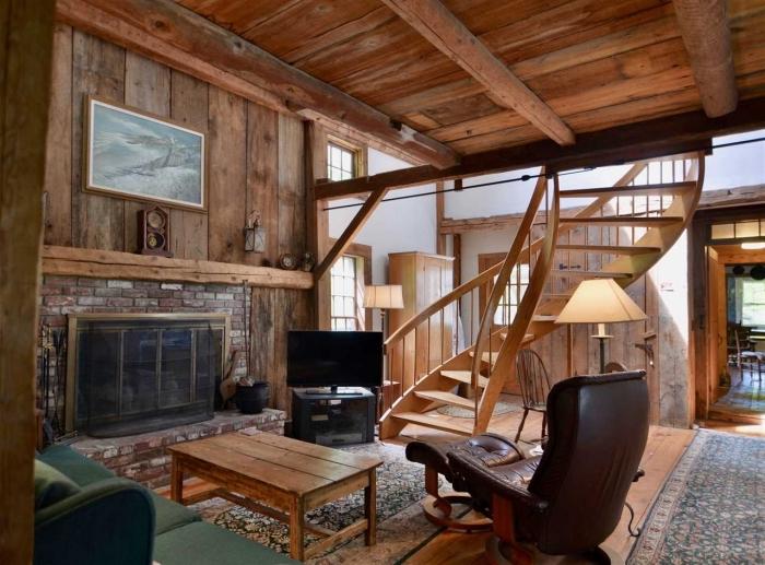 exemple de grange aménagée en maison, décoration salon rustique avec cheminée et meubles en cuir marron et bois