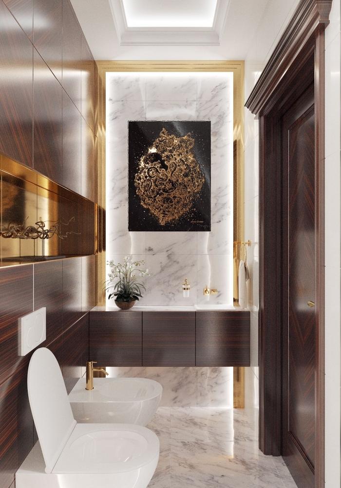 design luxueux dans toilettes avec revêtement mural marbre et bois foncé, décoration toilette avec accents dorés