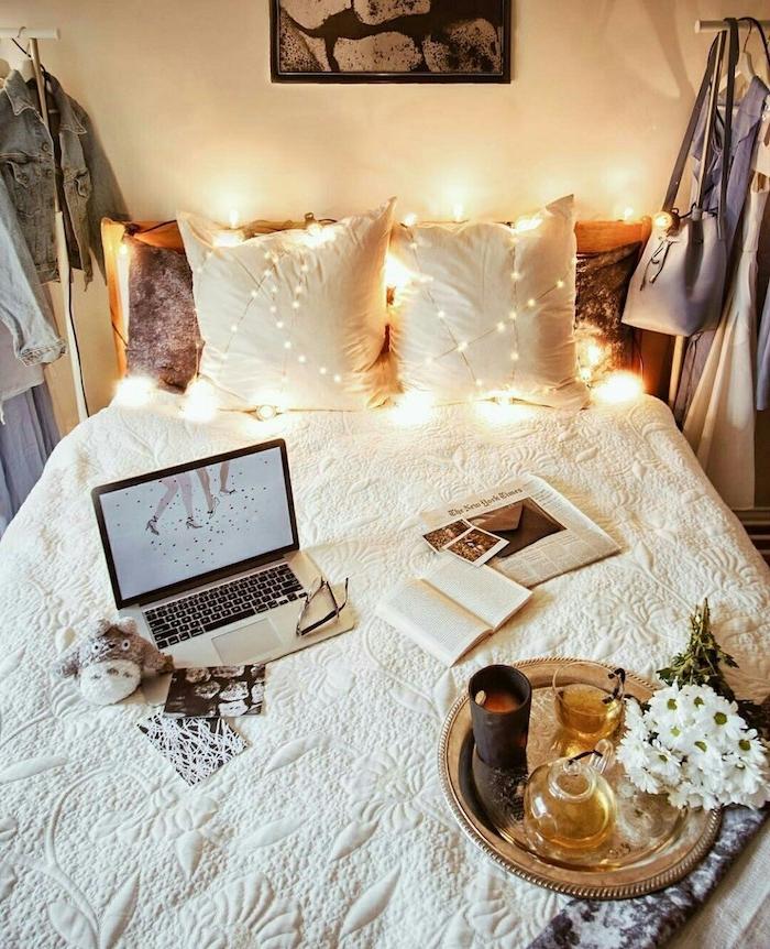 guirlande lumineuse deco lit cosy avec couverture blanche, dressing ouvert, tete de lit bous recyclé, plateau de service or, bougie bouruqet de fleurs, jouet totoro