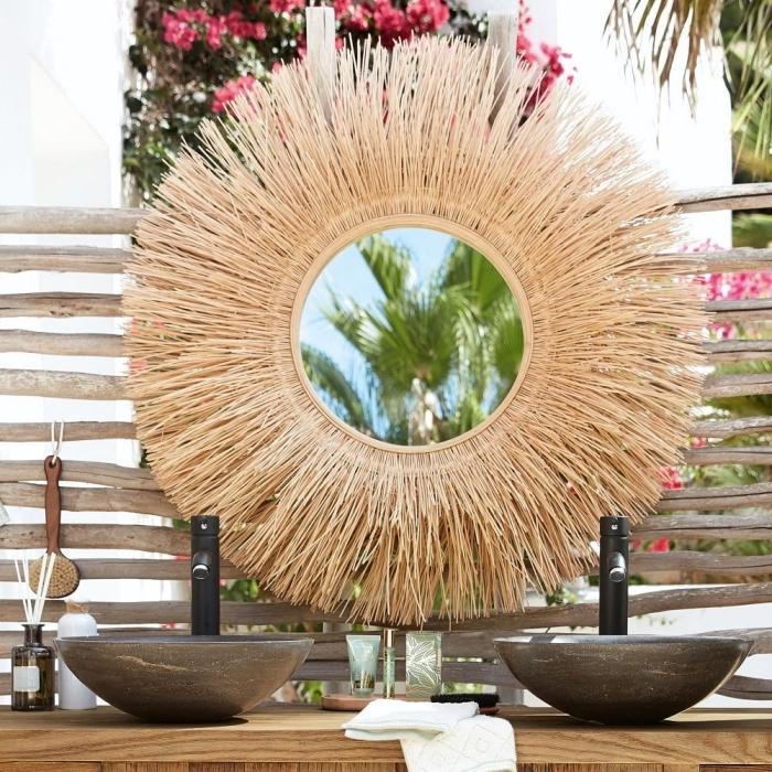 aménagement salle de bain extérieur avec objets en fibre végétale, modèle de miroir ovale à design soleil paille