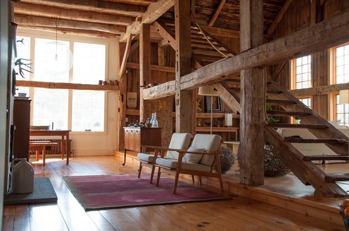 idée comble aménageable dans une grange mezzanine convertie, décoration salon aux murs et sol bois avec meubles bois