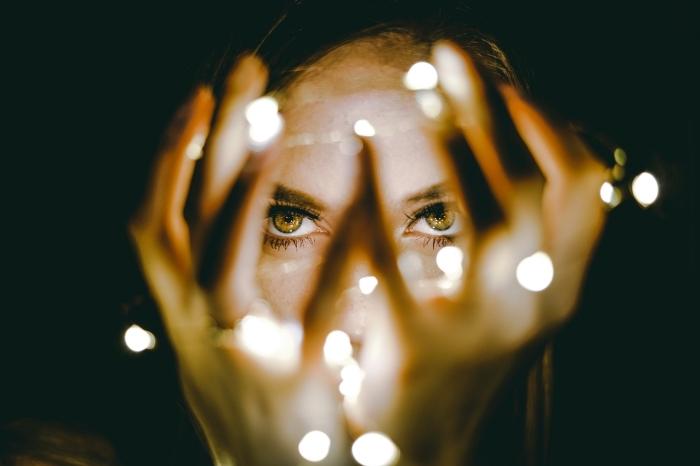 idée fond ecran halloween, photo visage fille aux cheveux balayés et yeux noisettes avec guirlande lumineuse dans ses mains