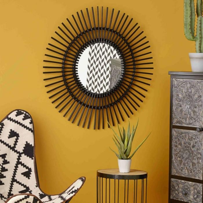 diy déco chambre avec miroir rond en forme soleil avec bâtonnets peints en noir mat, déco jungalow dans une pièce jaune