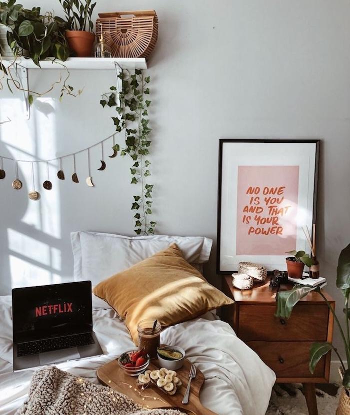 passer une soirée cosy dans un lit cocooning, table de nuit meuble bois, étagère blanche décorée de plantes, plaid marron, coussin jaune moutarde