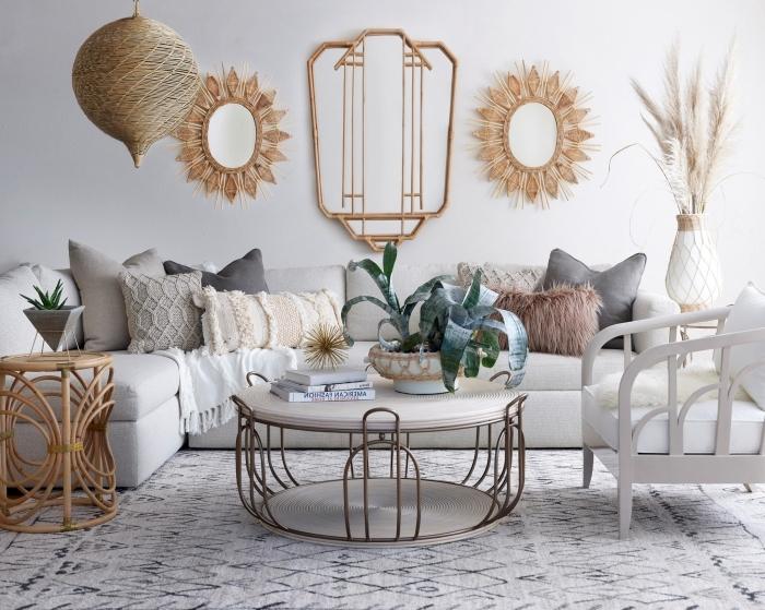 décoration de salon aux murs blanc aménagé avec canapé et table basse métal, modèle de table café en rotin, miroir en forme soleil