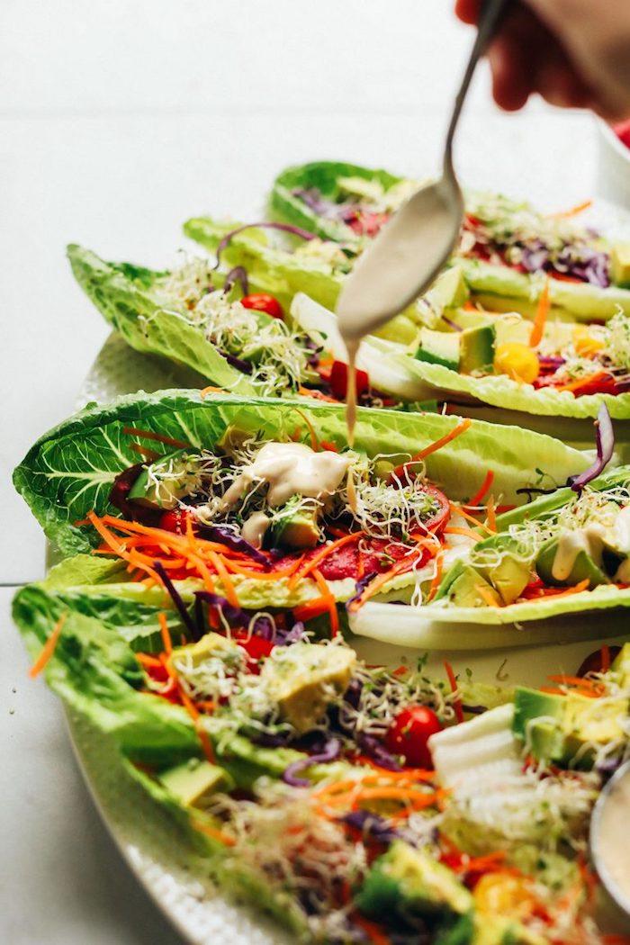 Idée recette rapide pour un apéro dînatoire, recette végétarienne de tacos arc-en-ciel en feuilles de laitue aux légumes frais garnis de hoummous et de sauce à la betterave