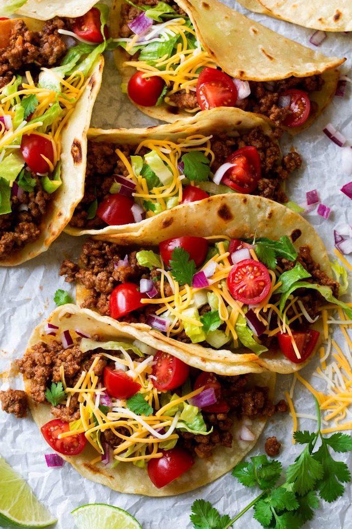 recette tacos maison à la viande de boeuf, cheddar râpé, tomates cerises et persil, wraps de tortillas mexicains parfaits pour une entrée facile et rapide