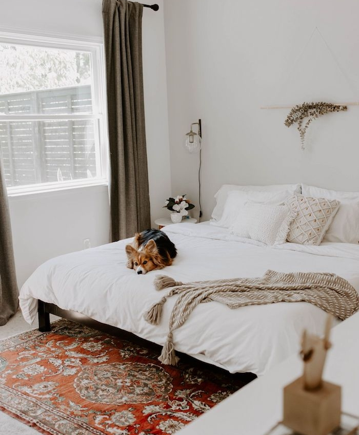tapis boheme chic dans une chambre aux murs blancs, linge maison blanc, chien mignon, couverture de lit grise, deco nordique
