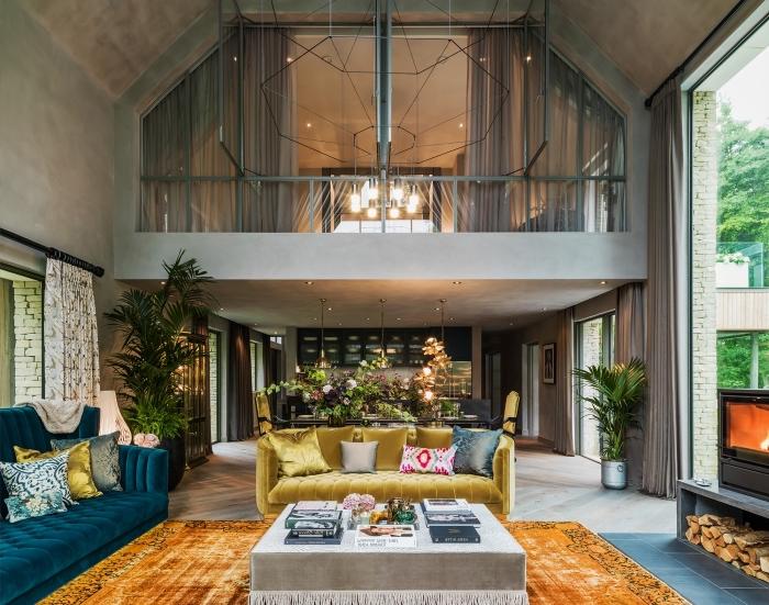design intérieur style moderne dans un loft mezzanine aux murs ciment et parquet bois gris, déco salon éclectique avec meubles en velours