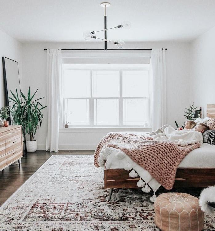 pouf marron, lit en bois avec linge maison blanc, plaid grosses mailles rose poudré, murs blancs, commede bois, tapis oriental usé