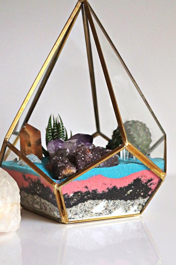 terrarium géométrique rempli de couches de sable couleur rose et bleu et décoré de cristaux