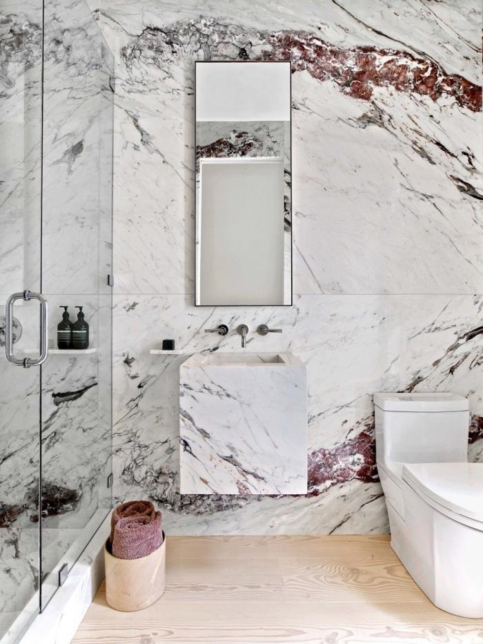 amenagement toilette moderne aux murs à effet marbre et sol effet bois, décoration toilette blanc et bois design luxueux