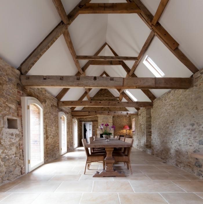 aménagement grange, design intérieur style rural aux murs pierre et poutres bois avec meubles en bois dans une salle à manger