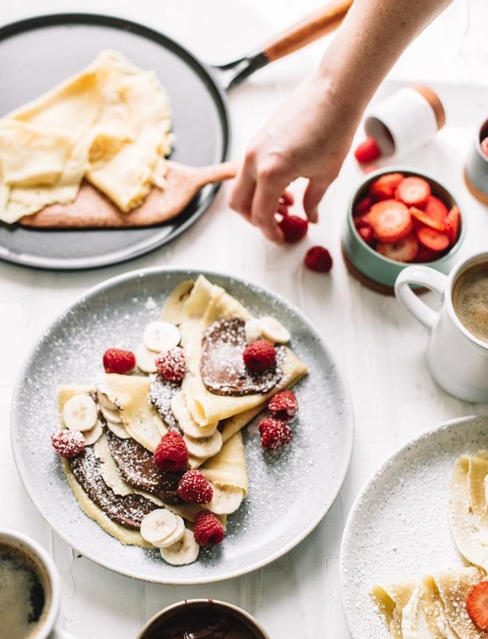 recette crepe sucré simple et traditionnelle tartinée de nutella et topping de fruits fraises, framboises, banane, sucre glace