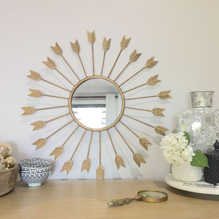 décoration de salon moderne aux murs blancs avec armoire en bois clair et objets ethniques, modèle miroir ovale doré