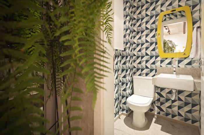 deco toilette petit espace aux murs habillées en carrelage motifs graphiques en nuances de gris et bleu avec accents jaune