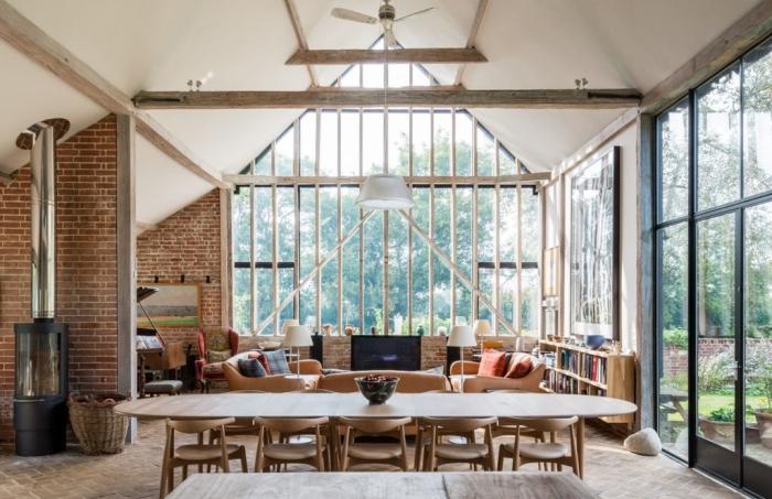 projet de renovation grange, aménagement salon loft au plafond blanc et bois avec meubles en cuir marron et accents bois
