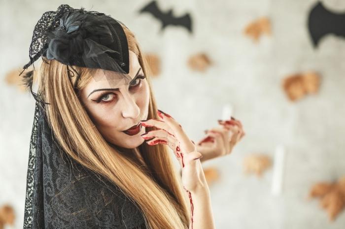 look d'Halloween pour femme, idée tenue vampire avec robe noire et accessoires cape et cheveux en dentelle