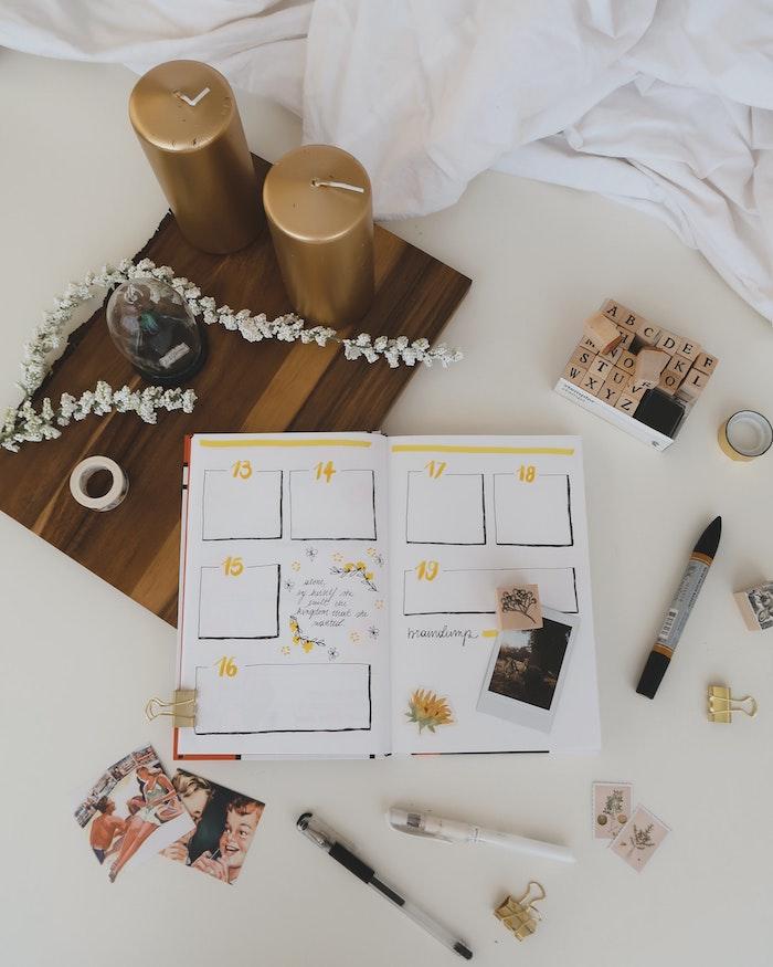 Astuces pour mieux gérer son temps, calendrier avec les dates importantes du mois, linge de lit blanc, bougies dorés