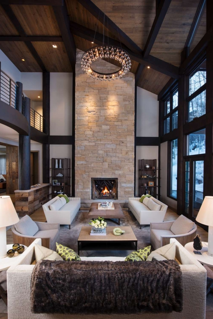 idée deco salon industriel et rustique aux murs blancs avec fenêtres noires et cheminée pierre, mobilier salon en cuir blanc