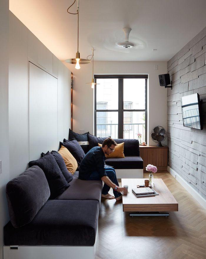 comment amenager un petit studio 20 m2, petit salon en longueur avec canapé d angle gris et blanc, table basse bois, mur de pierre parquet sol clair