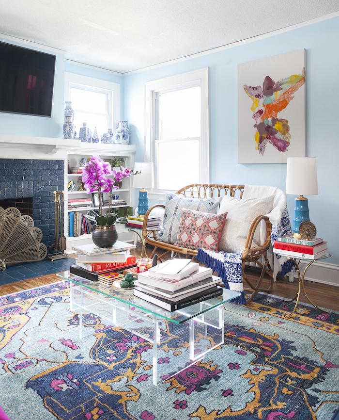 murs couleur bleu ciel, idée couleur de peinture pour salon moderne boheme chic, tapis coloré style oriental, canapé tressé, cheminée bleu marine, salon boheme artistique