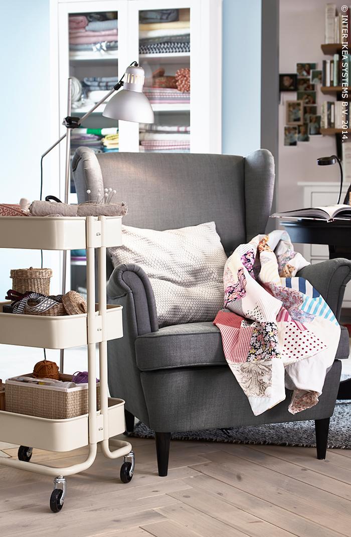 coin couture en fauteuil gris et etagere rangement outils et matériel de couture dans un salon abritant petit atelier de couture