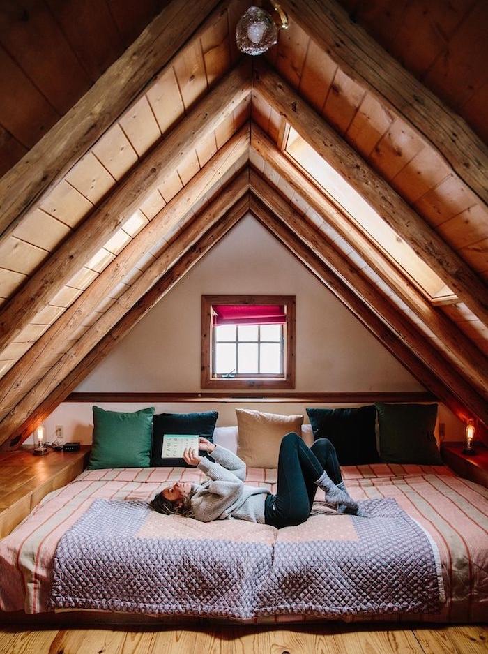 Maison en bois dans la montagne, fille liant un livre, lit sur le sol, petit chalet en bois, déco chalet montagne idée déco