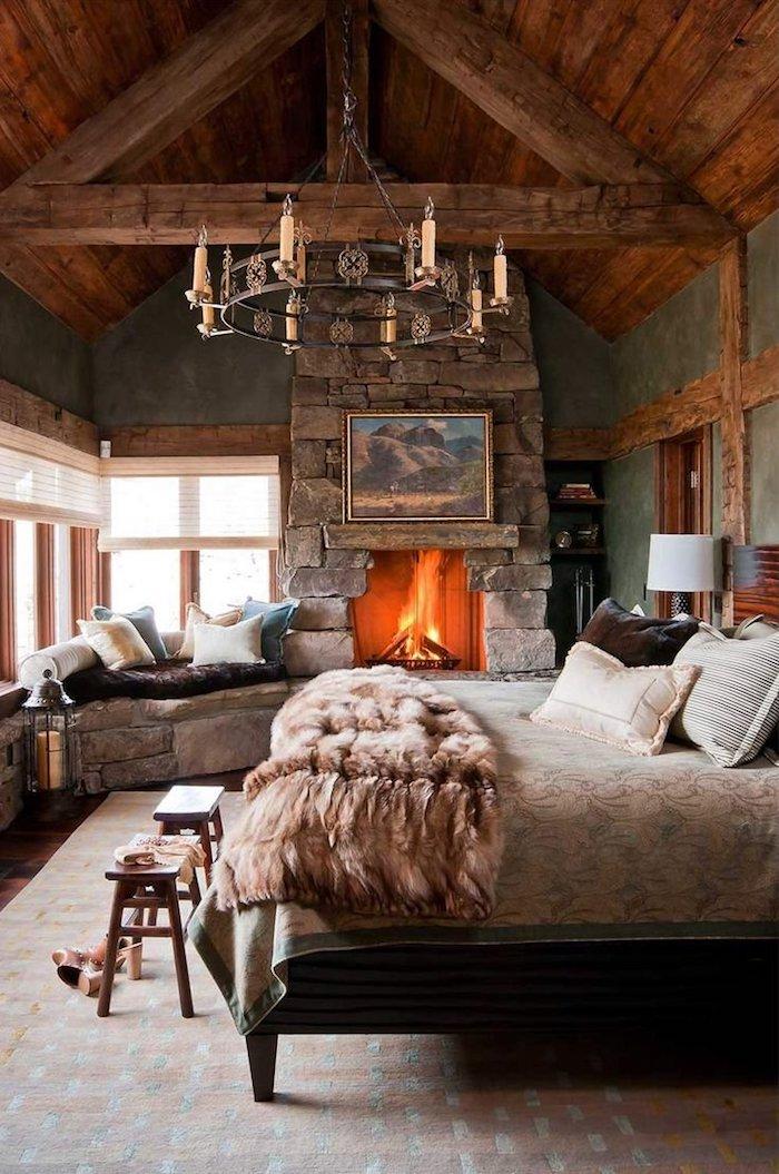 Cheminée allumée, lustre rustique en fer et bougies, chalet moderne, decoration esprit chalet montagne, lit grande pour la chambre à coucher cosy