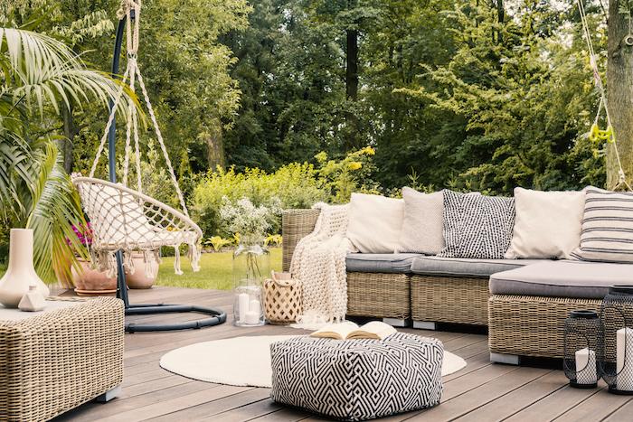 Salon de jardin design confortable, canapé d'angle en rotin, coussins cosy, balançoire dans le jardin, tapis rond