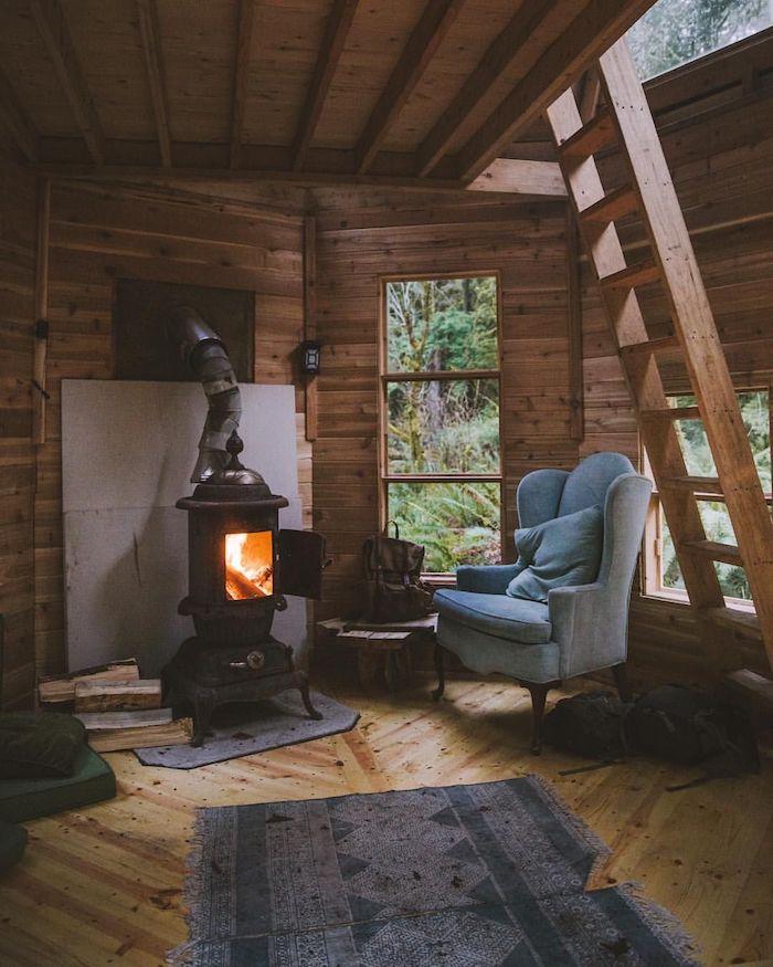 Cosy coin lecture avec fauteuil gris confortable près de la cheminée, decoration bois, deco montagne inspiration interieur chalet