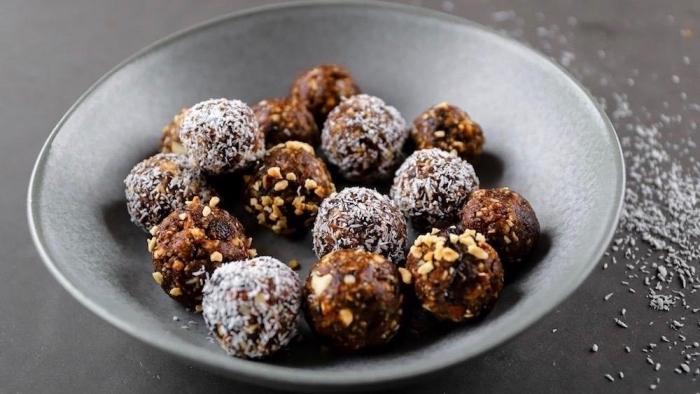 boules energie aux noix et fruits secs avec topping de noix ou flacons de coco rapée dans assiette grise
