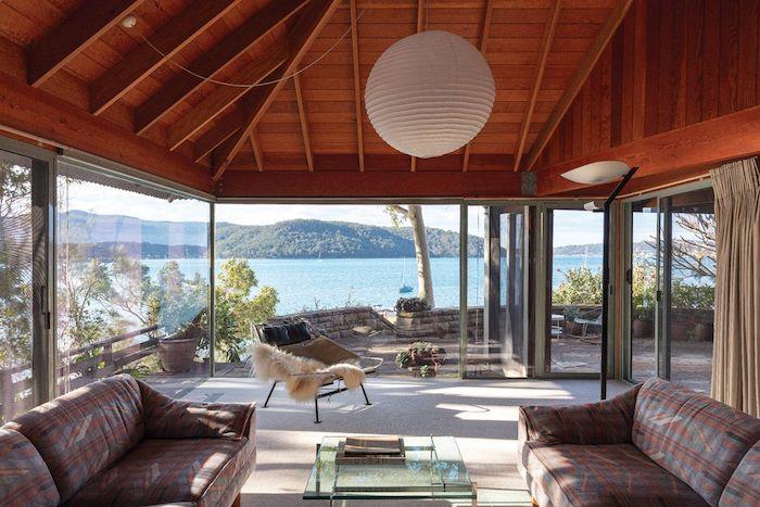 Vue magnifique de chalet au bord d'un lac, deco cocooning, deco chalet montagne cosy style nordique, deux canapés et table basse salon
