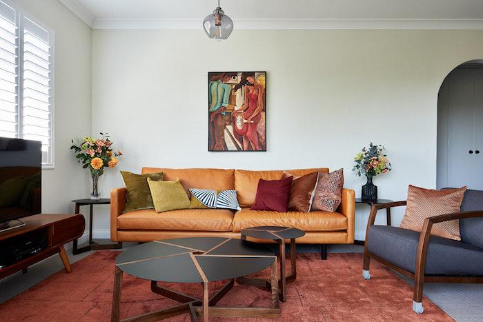canapé cuir marron clair, tapis marron, fauteuil gris foncé, table basse noire, fauteuil gris foncé, mur couleur blanc cassé