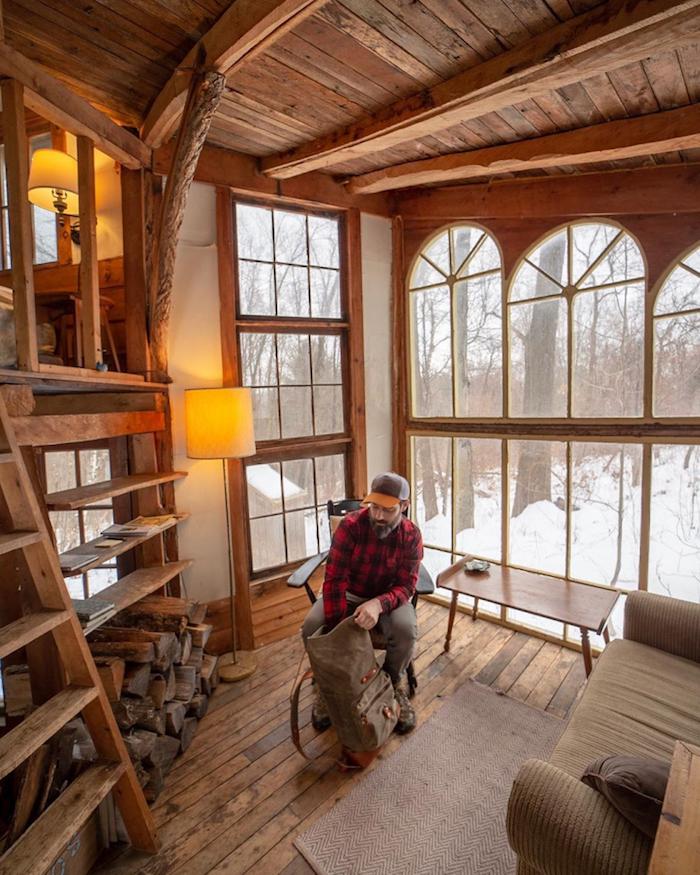 homme dans un petit salon dans beau chalet avec grandes fenetres, deco montagne chalet style scandinave, petit chalet en bois, canapé confortable, deux niveaux chalet, premier niveau salon, deuxième niveau chambre à coucher ouverte