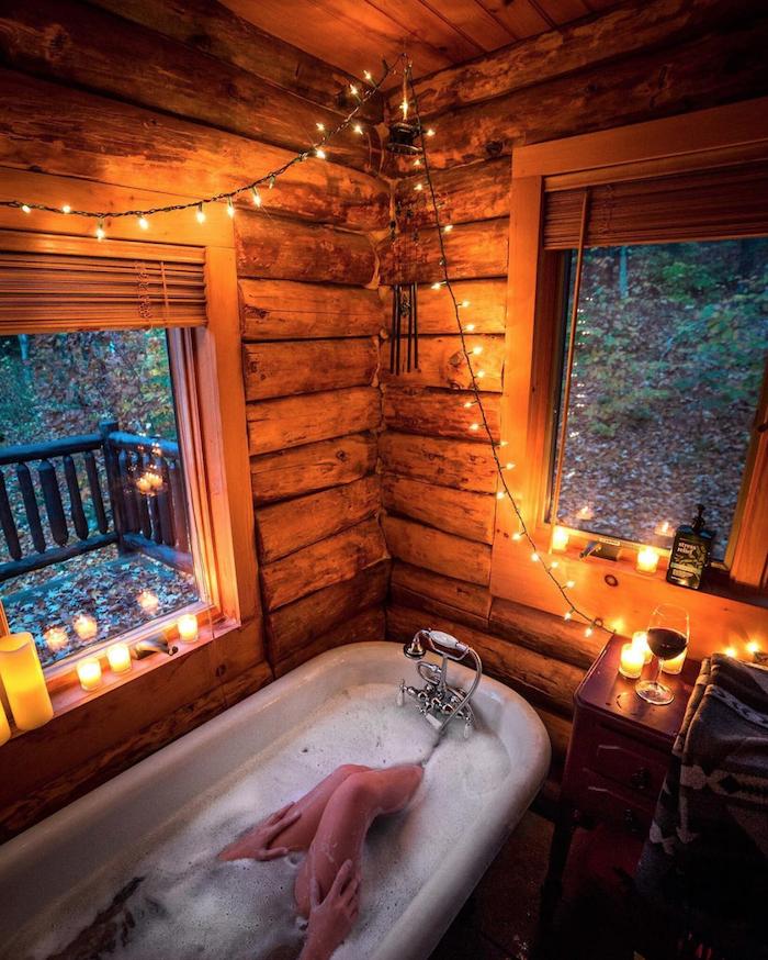 Baignoire deco chalet montagne, décoration scandinave en bois, salle de bain confortable avec guirlande lumineuse