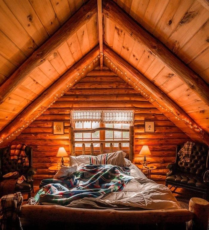 Bois intérieur décoré avec guirlandes lumineuses en haut du lit, petit chalet en bois, decoration bois maison rustique