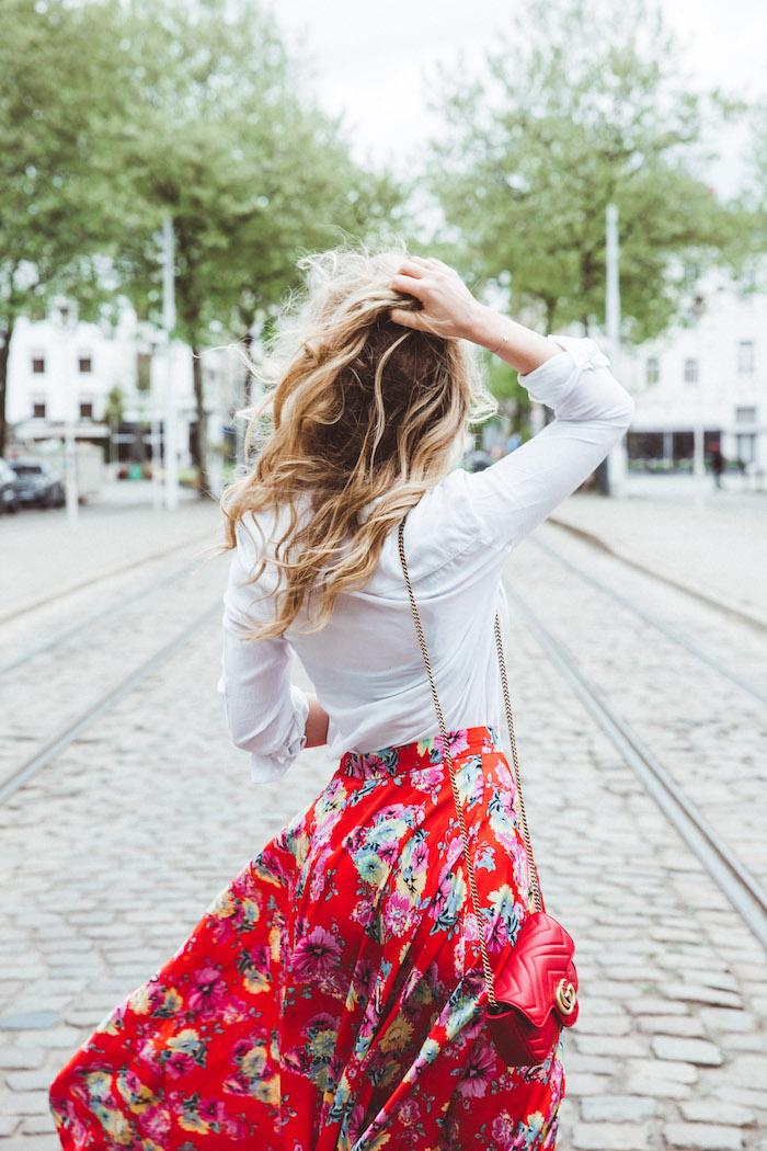 Rue avec ligne de tram, femme photo de dos, cheveux ondulés, jupe fleurie fluide et chemise blanche, comment porter une robe longue d'hiver en deux pièces