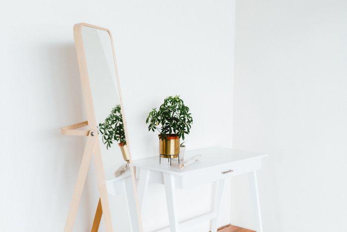 miroir grande taille, miroir en bois clair, plante verte d'intérieur sur une table d'appoint couleur blanche