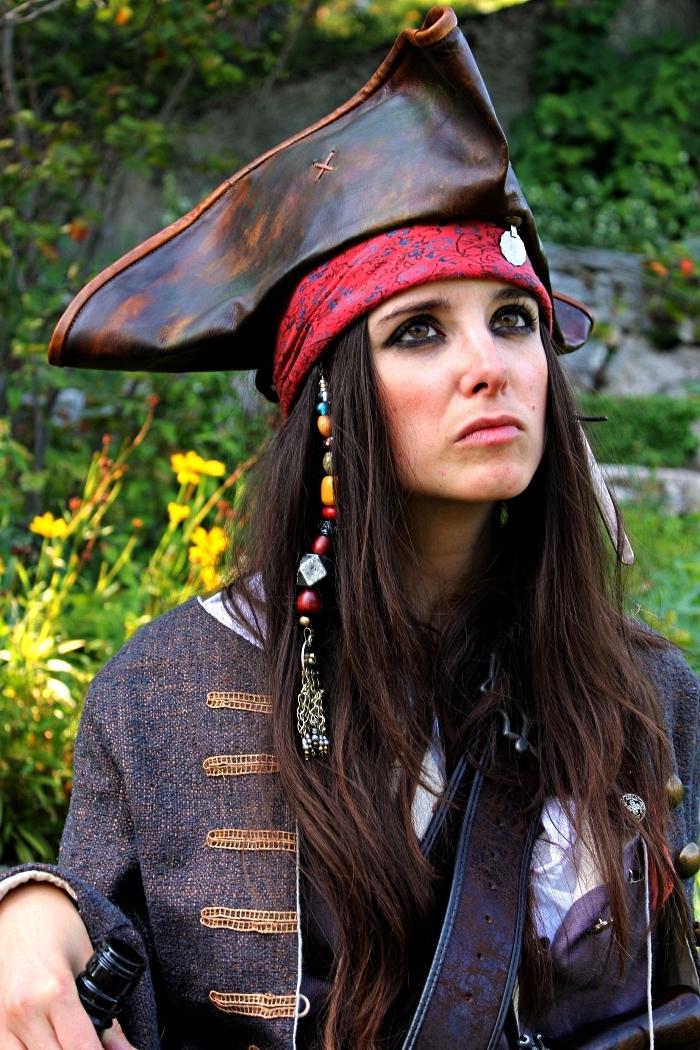 déguisement pirate femme avec chapeau en cuir, mèches à breloques et maquillage de pirate avec crayon noir, déguisement de jack sparrow pour femme