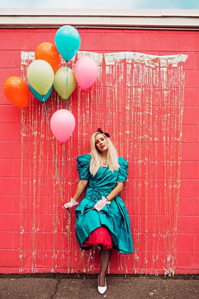 tenue de femme des années 80 en robe vintage bleu turquoise à manches bouffante, idée de coiffure disco des années 80
