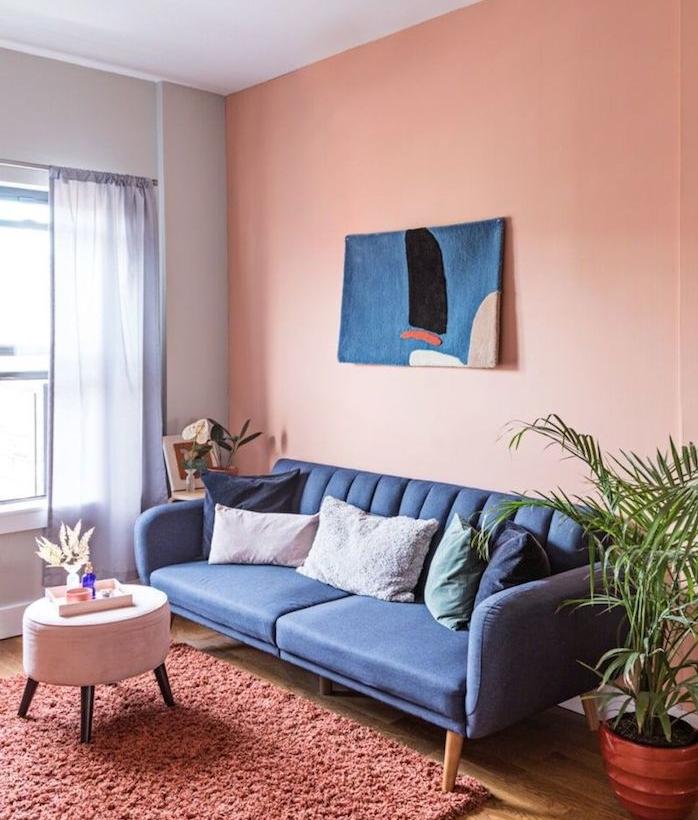 peinture couleur saumon dans un petit salon, murs accent saumon, canapé gris foncé, tapis rose foncé, table basse tabouret