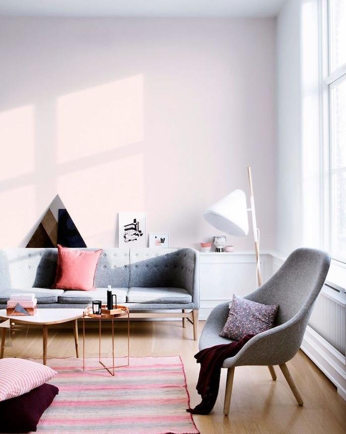 mur rose clair dans un grand salon gris, canapé et fauteuil gris, parquet bois clair, tapis à rayures coloré, amenagement salon cocooning